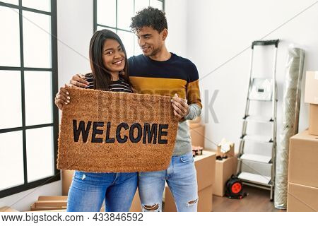 Young latin couple smiling happy holding welcome doormat at new home.