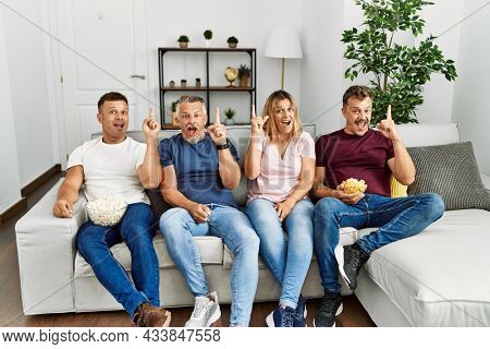 Group of middle age people sitting on the sofa at home pointing finger up with successful idea. exited and happy. number one.