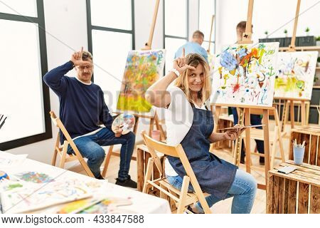 Group of middle age artist at art studio making fun of people with fingers on forehead doing loser gesture mocking and insulting.