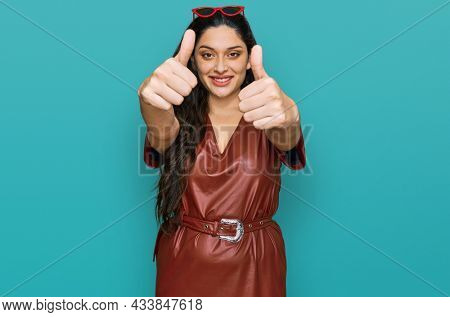 Brunette young woman wearing dress and sunglasses approving doing positive gesture with hand, thumbs up smiling and happy for success. winner gesture.