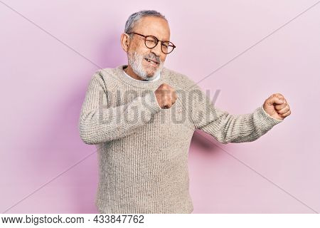 Handsome senior man with beard wearing casual sweater and glasses dancing happy and cheerful, smiling moving casual and confident listening to music