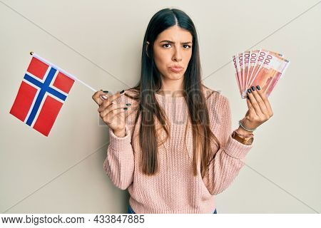 Young hispanic woman holding norway flag and krone banknotes skeptic and nervous, frowning upset because of problem. negative person.
