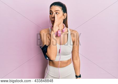Young hispanic woman wearing gym clothes and using headphones hand on mouth telling secret rumor, whispering malicious talk conversation