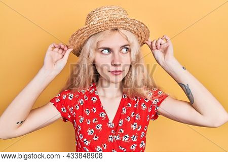 Beautiful caucasian woman with blond hair wearing summer hat smiling looking to the side and staring away thinking.
