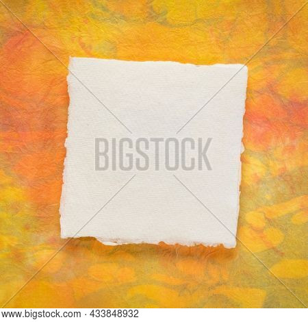 small sheet of blank white Khadi rag paper from South India against orange and yellow marbled paper