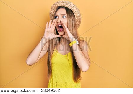 Young blonde girl wearing summer hat shouting angry out loud with hands over mouth