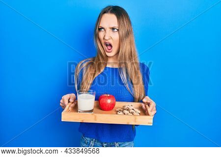 Young blonde girl holding tray with breakfast food angry and mad screaming frustrated and furious, shouting with anger. rage and aggressive concept.
