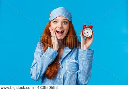 Excited Young Girl Wake Up On Time, Holding Red Cute Clock Set Alarm And Smiling Amused, Wearing Nig