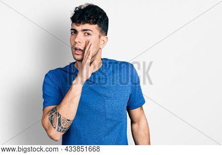Young hispanic man wearing casual t shirt hand on mouth telling secret rumor, whispering malicious talk conversation