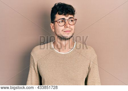 Young hispanic man wearing casual clothes and glasses smiling looking to the side and staring away thinking.