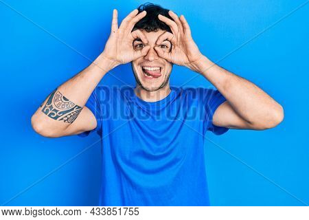 Young hispanic man wearing casual blue t shirt doing ok gesture like binoculars sticking tongue out, eyes looking through fingers. crazy expression.