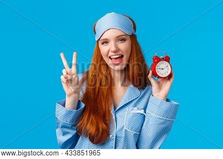 Sassy And Cheeky Confident Redhead Caucasian Female In Nightwear, Sleep Mask, Showing Red Alarm Cloc