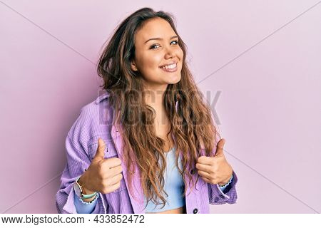 Young hispanic girl wearing casual clothes success sign doing positive gesture with hand, thumbs up smiling and happy. cheerful expression and winner gesture.
