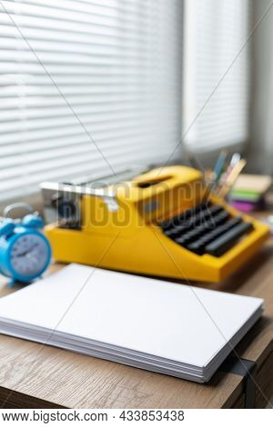 Stack sheet of paper and vintage old typewriter at wood desk table. Writer or study creative