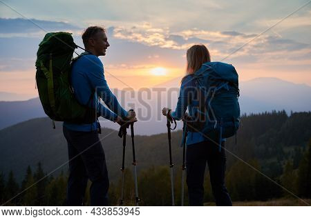 Husband Happy Looking At His Wife Who Admiring View Of Mountain Peaks And Cloudy Evening Sky. Back V