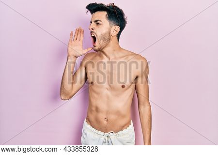 Young hispanic man wearing swimwear shirtless shouting and screaming loud to side with hand on mouth. communication concept.