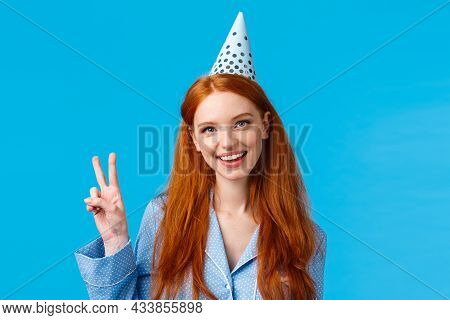 Lucky And Enthusiastic Feminine Pretty Redhead Woman With Long Curly Hair In Nightwear, Wearing Birt