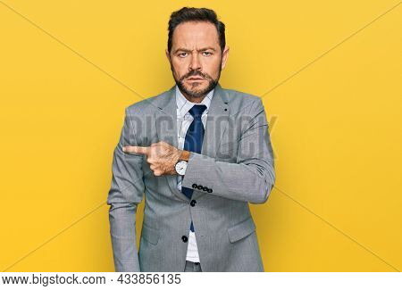 Middle age man wearing business clothes pointing aside worried and nervous with forefinger, concerned and surprised expression
