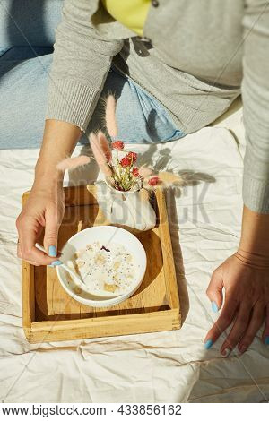 Breakfast In The Bed, Woman In Jeans Sitting On The Bed, And Eating Healthy Granola Bowl