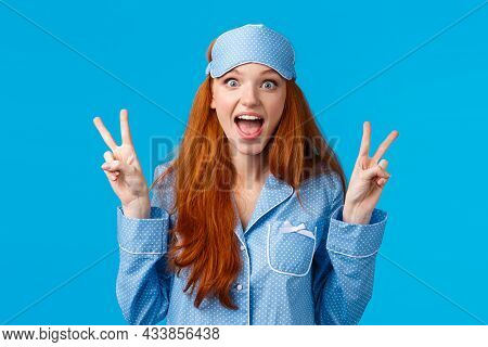 Excited Cute Redhead Girl In Sleep Mask And Pyjama Showing Peace Signs And Screaming Thrilled Overwh