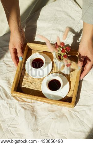 Breakfast In Bed, Female Hands Put Try With Two Cups Coffee And Flower In Sunlight