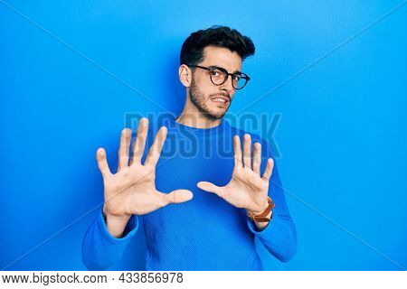 Young hispanic man wearing casual clothes and glasses disgusted expression, displeased and fearful doing disgust face because aversion reaction. with hands raised
