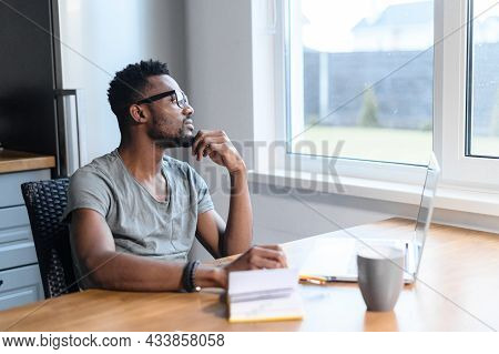 An Intelligent African-american Young Man In Glasses And Casual Shirt Sits At The Kitchen Desk With