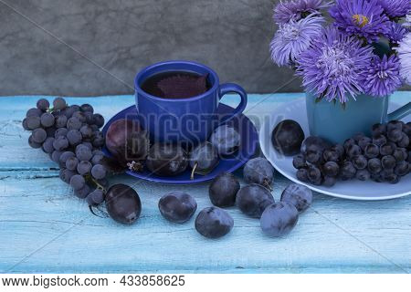 Still Life In Blue Tones. There Is A Bouquet Of Blue Asters In The Cup. Nearby Is A Cup Of Tea With