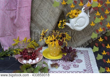 Pour Autumn Into A Cup. A Hand Holds A Teapot, From Which Yellow Flowers Are Pouring Into A Yellow C