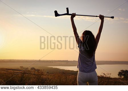 Woman Raising Hands With Elbow Crutch Up To Sky Outdoors At Sunrise, Back View. Healing Miracle