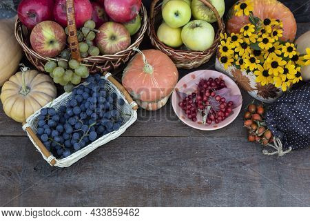 View From Above. On A Dark Background, There Are Baskets With Red And Yellow Apples, A Bouquet Of Ye