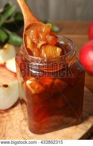 Spoon With Tasty Apple Jam In Glass Jar On Wooden Board, Closeup