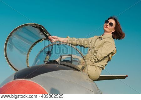 Portrait of a beautiful woman pilot in uniform and sunglasses posing in her fighter jet happily smiling in the background of the bright blue sky. Military aircraft.