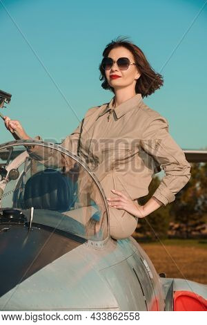 Professional commercial pilot woman wearing uniform and sunglasses posing in her aircraft cockpit happily smiling with a sense of pride. Aviation.