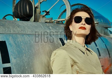 Portrait of a female pilot with red lips wearing uniform and sunglasses leaning to her fighter jet and looking up into the bright blue sky. Civil and military aviation.