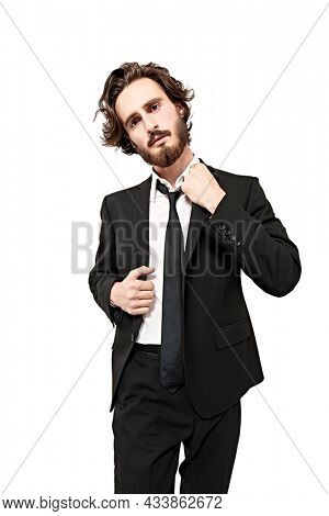 Portrait of a handsome well-groomed man posing in a smart black suit and white shirt. Studio portrait in a white background. Men's fashion.