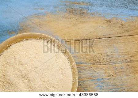 small ceramic bowl of African baobab fruit powder against grunge painted wood background with copy space