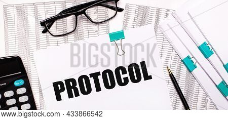 On The Desktop Are Reports, Documents, Glasses, A Calculator, A Pen And Paper With The Text Protocol