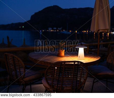 Dining Table On The Embankment At Night, Romantic Dining In Luxury Resort. Cafe On Beach With Seavie