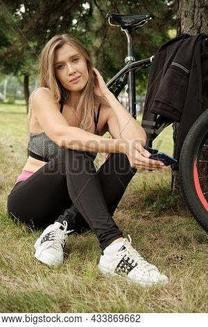 Young Woman Biker With Phone Relaxing Sitting On Grass