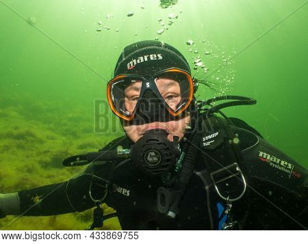 September 5, 2021 - Malmo, Sweden: A Female Scuba Diver Lit Up By Rays Of Sunlight Penetrating The W