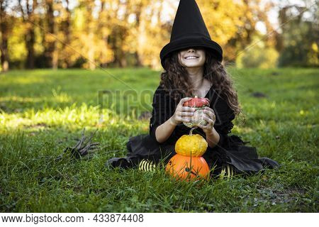 Adorable Little Girl With Hair In Black Witch Hat Making Grimace, Holding Pumpkins, On A Sunny Autum