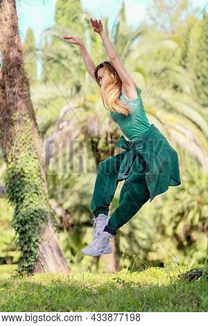 Hiphop Girl In Emerald Outfit In Pose Flies In A Jump In A Green Park On A Summer Day