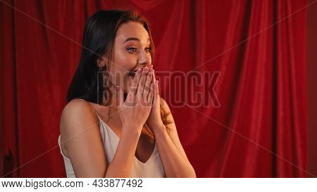 Stunned Young Woman Covering Mouth On Red.