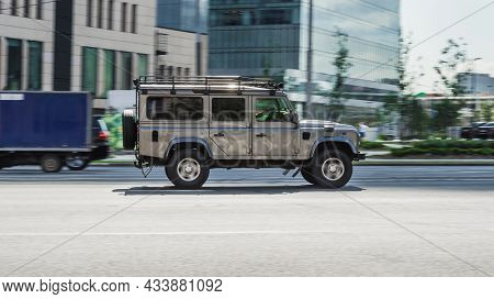 Land Rover Defender 110 Is Driving On Moscow Streets With Blurred Background. Fast Moving Gray Color