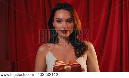 Pleased Young Woman Holding Gift Box On Red.