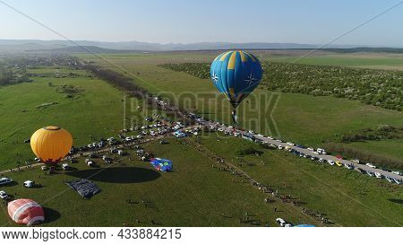 Top View Of Field With Balloons. Shot. Colorful Balloons In Field. Preparing For Balloon Festival In