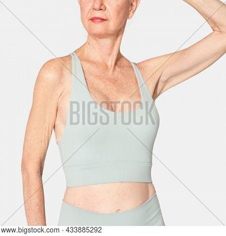 Healthy senior woman in mint green sports bra and leggings