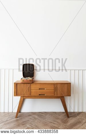 Vinyl player in a portable turntable on a wooden sideboard table