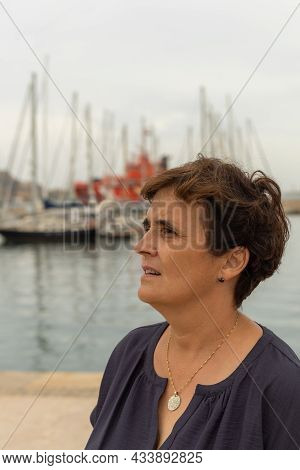 Caucasian Adult Female Caucasian Looking To The Side Near A Harbor With Moored Boats